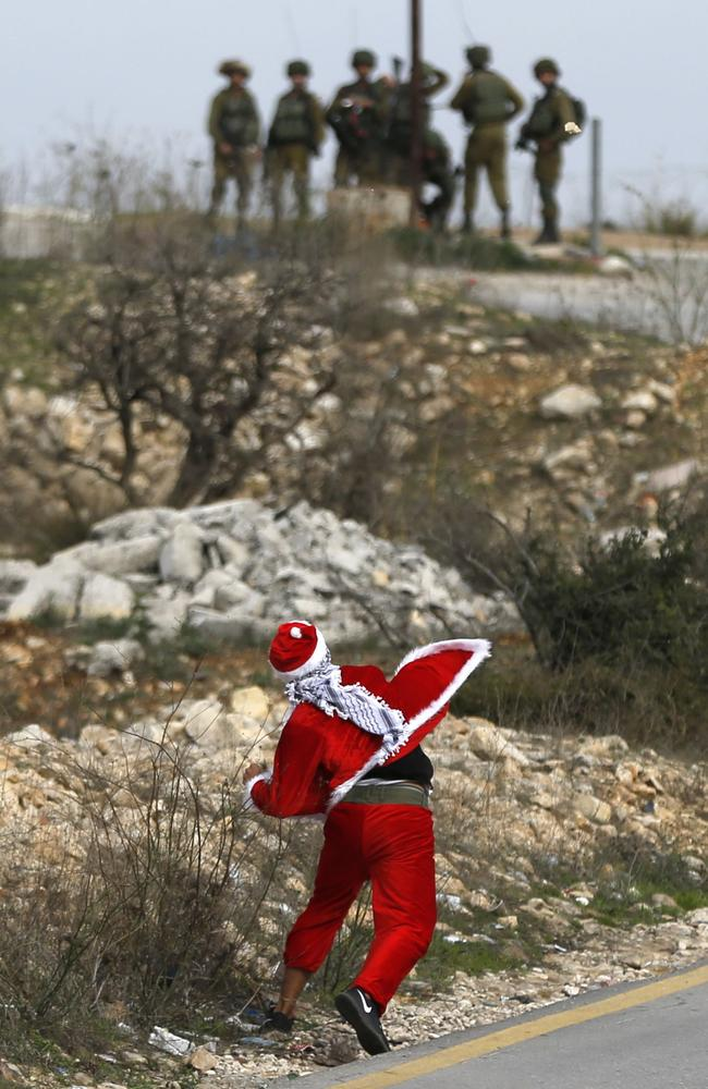 A Palestinian protester dressed-up as Father Christmas throws stones towards Israeli soldiers during clashes at Atarot checkpoint on the northern outskirts of Jerusalem. Picture: AFP