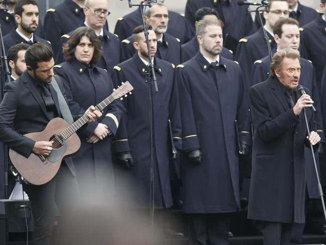 French rock star Johnny Hallyday, right, sings backed by an army choir. Picture: Michel Euler/AP