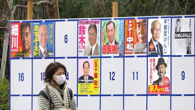 On strike...A woman walks in front of a board displaying candidates for the Tokyo gubernatorial election. Picture: AFP