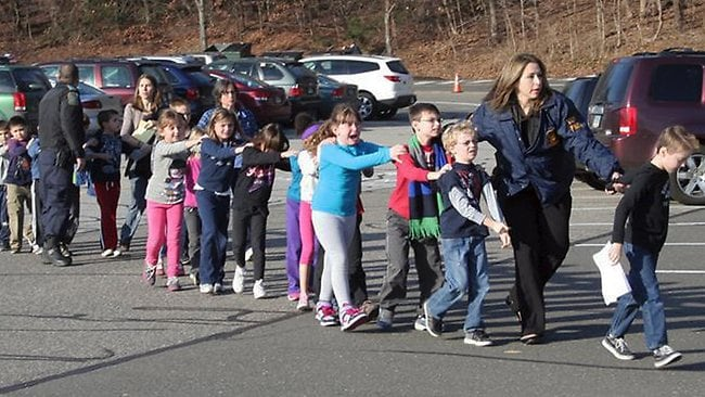 Connecticut State Police lead children from the Sandy Hook Elementary School. Picture: AP/ Newtown Bee
