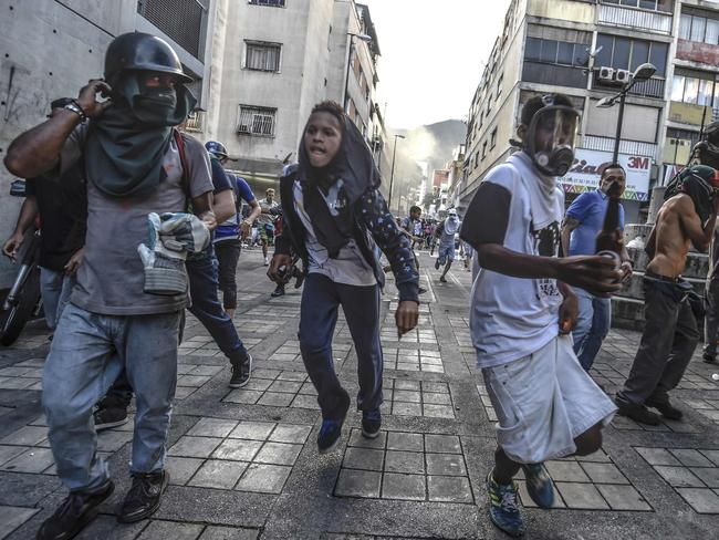 Anti-government activists scatter upon being charged by riot police in Caracas. Picture: AFP