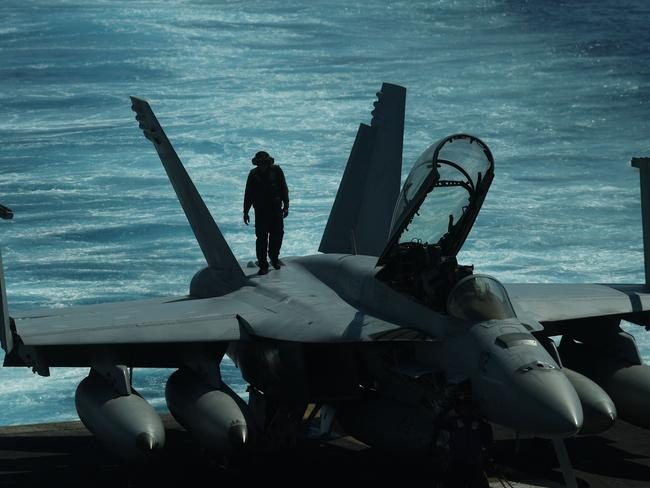 A sailor inspects atop an FA-18 hornet fighter jet during a routine training aboard US aircraft carrier Theodore Roosevelt in the South China sea which is transiting after participating in operations in Syria, Iraq and Afghanistan. Picture: AFP PHOTO / TED ALJIBE