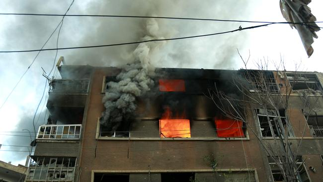 Fire flames rip through a building following Syrian government bombardment in the town of Douma. Picture: AFP PHOTO / Hamza Al-Ajweh