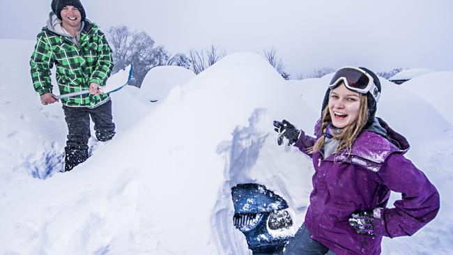 Sally McLaren, 24, and Tom Pappas, 23, have to dig their car out of th snow at Falls Creek. Picture: Jason Edwards.