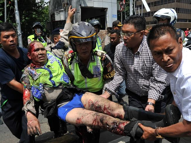 An injured Indonesian policeman ... evacuated from the site of a bomb blast in front of a