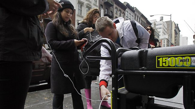 People in New York's Tribeca neighborhood wait for a chance to charge their mobile phones on an available generator setup on a sidewalk. Picture: Richard Drew