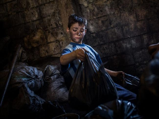 "Talal Louai, packs charcoal into 2kg bags. In his home town of Homs, Talal was top of his class. ""I miss school, especially science, I want to be a surgeon,"" he says. ""I am very bored here, I want to go back to Syria so I can go to school."" But he is proud to be helping his family. Picture: UNHCR / Andrew McConnell"