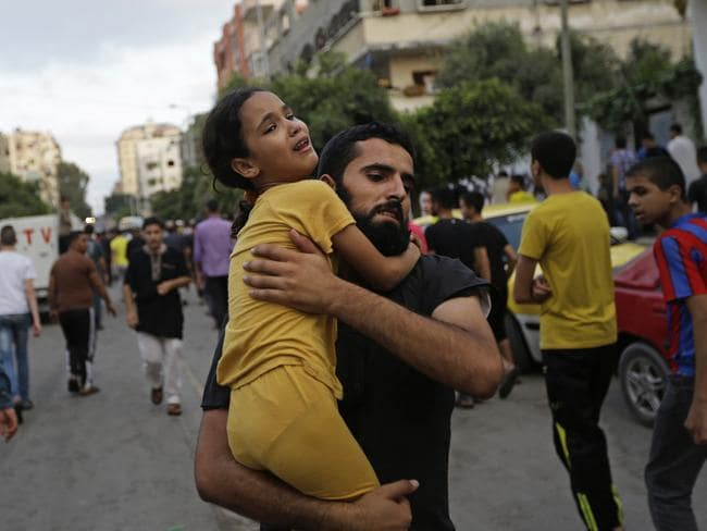 Children and civilians have paid an overwhelmingly high price in the current conflict. Pictured, a Palestinian man carries away a girl during the funeral of a seven year old boy killed in an explosion at a refugee camp. Pic: Lefteris Pitarakis.
