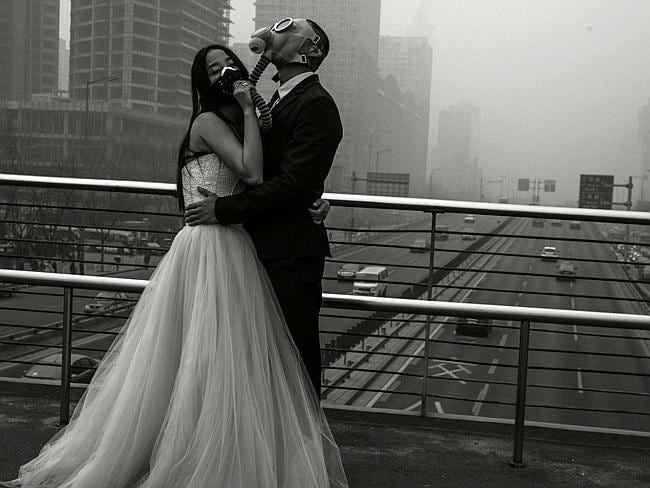 Polluted ... The newlyweds embrace above one of Beijing's major freeways during this week's this smog and pollution.