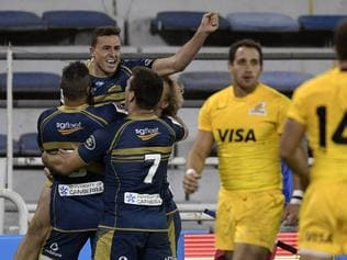 Australia's Brumbies fullback Thomas Banks (top) celebrates with teammates after scoring the team's third try against Argentina's Jaguares during the Super Rugby match at Jose Amalfitani stadium in Buenos Aires, Argentina on May 27, 2017. / AFP PHOTO / JUAN MABROMATA