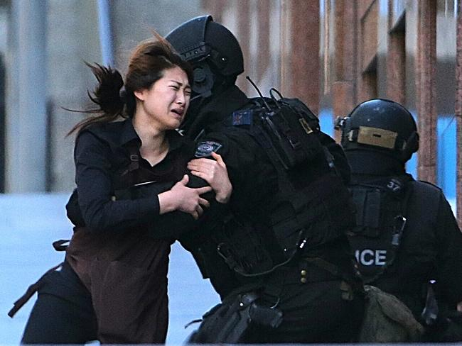 A hostage runs to armed tactical response police officers for safety after she escaped from a cafe under siege at Martin Place. Picture: AP Photo/Rob Griffith