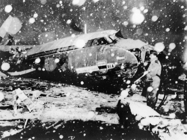 A rescue worker stands next to the debris of the plane that crashed after taking off from Munich airport on February 7, 1958 during a snowstorm.