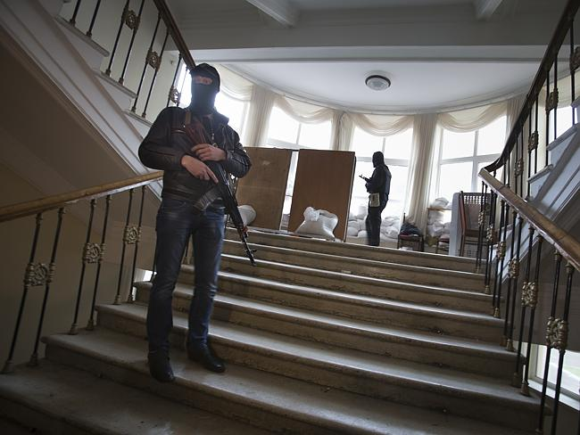 Buildings taken over ... Pro-Russian gunmen guard inside an administration building they seized in Luhansk, one of the largest cities in eastern, Ukraine.