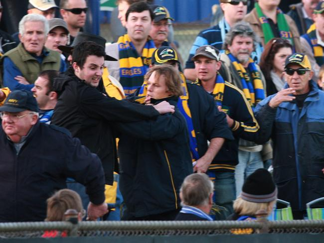 Eagles footballer Leigh Treeby grapples with Sturt fan Luke Grant at Woodville Oval in 2010.