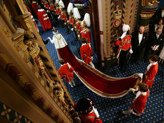 Grand entrance ... page boys carry Queen Elizabeth's train as she and Prince Philip proceed through the Royal Gallery. Picture: Yui Mok