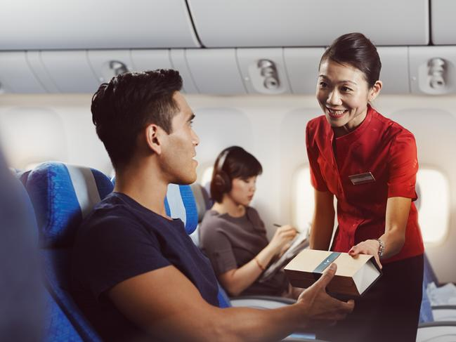 Cathay Pacific economy class - serving a snack to a passenger