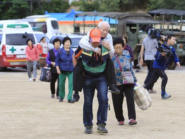 Flee to safety....Residents arrive at a shelter to avoid a gunfight between South Korean army soldiers and the runaway soldier. Picture: AP