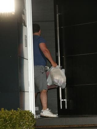 A man drops off a bag of chicken at the Ibrahim Dover Heights home on Wednesday night. Picture: Richard Dobson