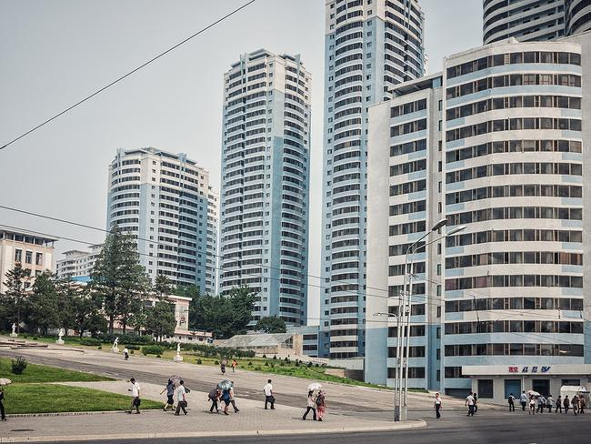 People walking past skyscrapers in Pyongyang. Picture: Michal Huniewicz /Exclusivepix Media