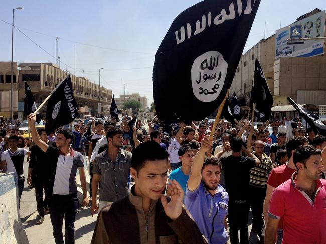 Demonstrators chant ... pro-Islamic State group slogans as they carry the group's flags in front of the provincial government headquarters in Mosul, Iraq. Picture: AP