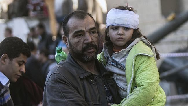 An Egyptian man carries an injured girl at the site of a car bomb explosion outside the Cairo police headquarters. Picture: AFP
