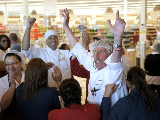 We've won ... Market Basket meat manager Bob Dietz, centre, raises his arms in celebration.