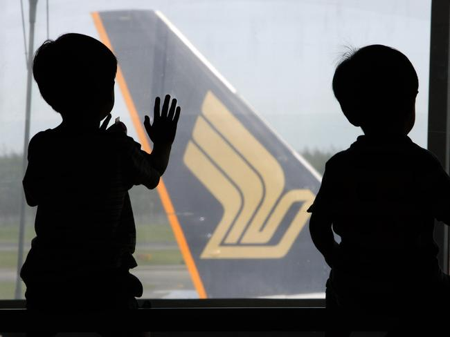 Children view a Singapore Airlines plane.