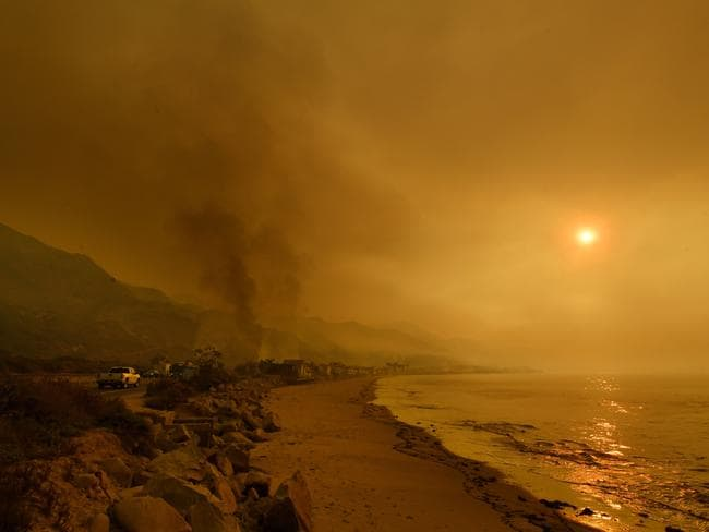 Heavy smoke covers the seaside enclave of Mondos Beach beside the 101 highway as flames reach the coast near Ventura, California. Picture: AFP/Mark Ralston