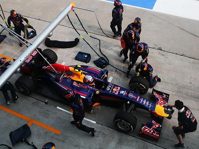 Daniel Ricciardo's Red Bull car is pushed back into its pitxbox by the team's crew member