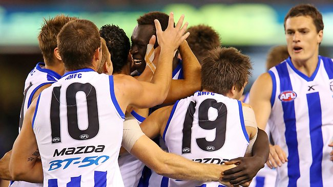 North Melbourne players celebrate Majak Daw's first ever AFL goal. Picture: George Salpigtidis