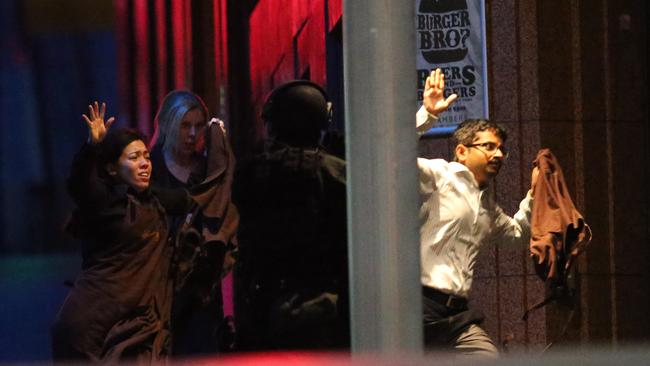 Hostages run to safety during the cafe siege. Picture: AP Photo/Rob Griffith