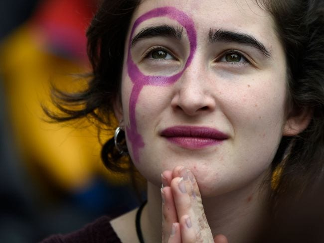A girl with a Venus symbol on her face attends a protest in Barcelona. Photo: AFP / Lluis Gene