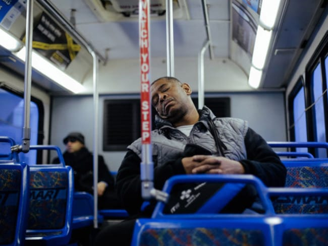 James Robertson sleeps on the bus he rides part of the way home in the middle of the night.