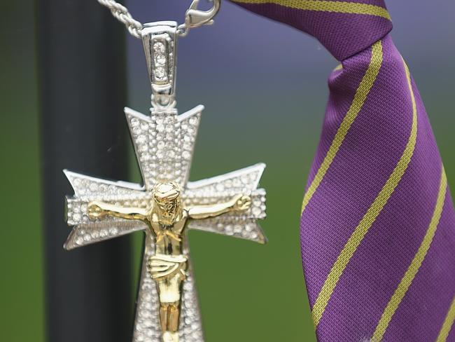 Tributes ... a crucifix and school tie hang on the fence outside Corpus Christi Catholic College, after a 15-year-old student was been arrested in connection with the death of teacher Ann Maguire. Picture: Christopher Furlong