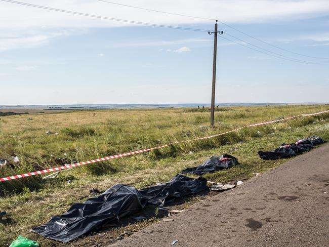 Mapping the site ... the bodies of MH17 victims awaited collection by the side of the road near Grabovo. Picture: Brendan Hoffman/Getty Images