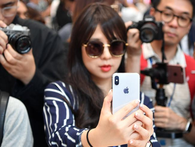 People take photos as a woman tests out a new iPhone X during a media event at Apple's new headquarters. Picture: AFP