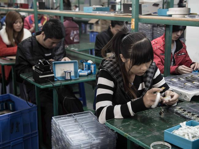 A woman puts an MP3 player together in another factory. Picture: Kate Davies/Unknown Fields.