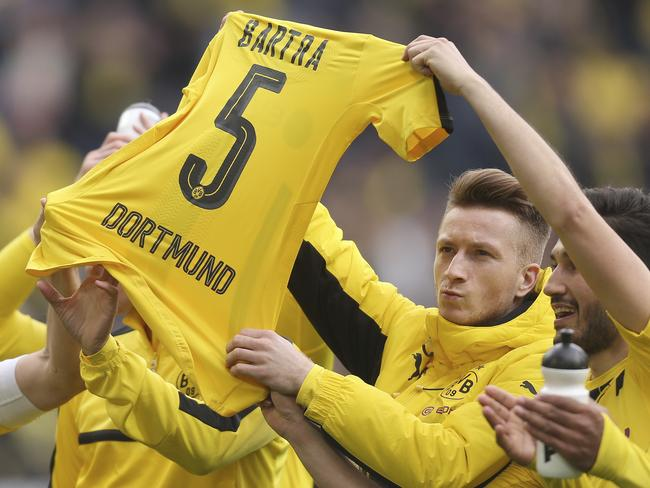 Dortmund's Marco Reus and Nuri Sahin hold up the jersey of teammate Marc Bartra.