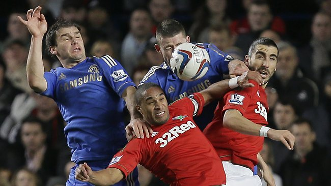Chelsea's Branislav Ivanovic, left with teammate Gary Cahill, jump to head the ball with Swansea City's Wayne Routledge, and Chico Flores, right, in the English League Cup semi-final first leg at Chelsea's Stamford Bridge stadium. Picture: Alastair Grant