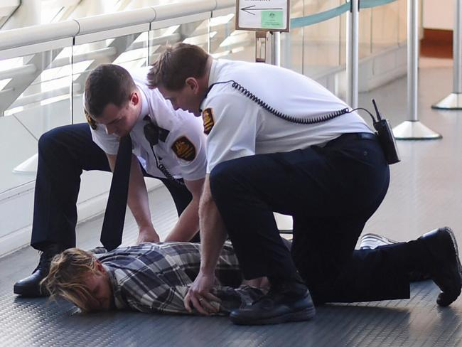Officials pin one of the refugee activists to the ground at Parliament House in Canberra. Picture: Lukas Coch/AAP