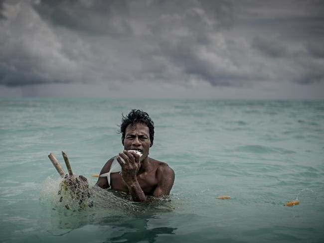 A man bites to kill a fish he caught in a fishing net. Fishing has been the main diet of Kiribati but in recent years, the fish population has decreased in the oceans and it becomes increasingly difficult to live on fishing. Picture: Jonas Gratzer
