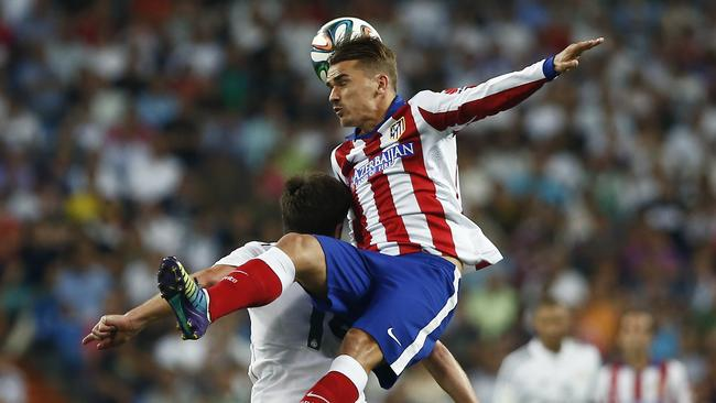 Atletico's Antoine Griezmann, top, competes for the ball with Real's Xabi Alonso.