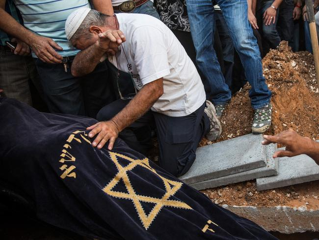 Bloodshed. a mourner weeps over the body of Israeli Dror Khenin as he is lowered into the ground at a cemetery after his funeral on July.