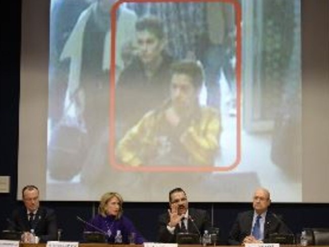 Interpol officials sit in front of CCTV images of the Iranian passengers travelling on MH370 on fake passports. Picture: AFP