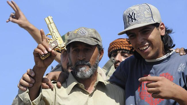Second-rate Bond villain: The golden gun Gaddafi was found holding when he was captured cowering in a storm drain. Picture: AP