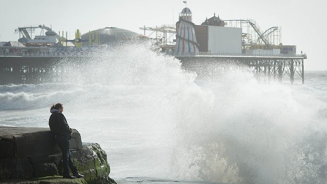 Large waves break against barriers on the seafront in Brighton, southern England on October 27, 2013 as a predicted storm starts to build. Britain was braced on October 27 for its worst storm in a decade, with heavy rain and winds of more than 80 miles (130 kilometres) an hour set to batter the south of the country. AFP PHOTO / LEON NEAL