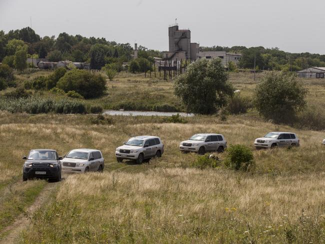 Investigation ... Vehicles transporting observers from the Organisation for Security and Co-operation in Europe (OSCE) drive through the main crash site of Malaysia Airlines flight MH17 in Grabovo, Ukraine. Picture: Getty