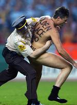<p>A Spanish police officer apprehends a streaker who ran onto the pitch during the UEFA Cup final between Glasgow Celtic and FC Porto at the Olympic Stadium in Seville, Spain.</p>