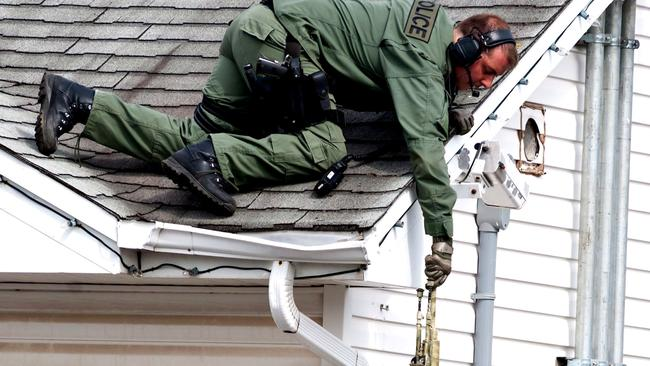 A weapon is passed to an Emergency Response Team member on the roof of a house in Moncton as the search continues. Picture: AP Photo/The Canadian Press.