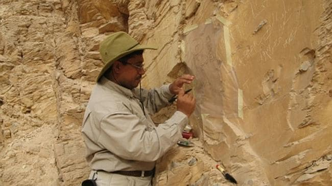 Afifi Ghonim traces ancient 'graffiti' off a cliff in the Valley of the kings. Picture: Afifi Ghonim